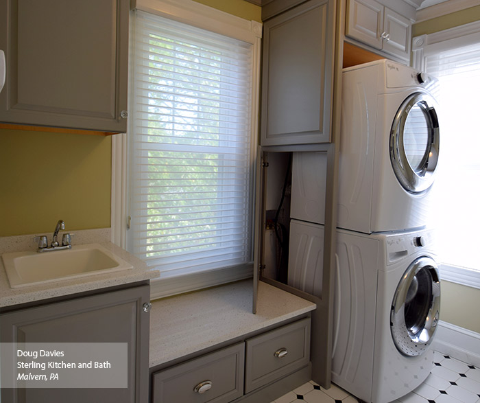 Gray laundry room cabinets with panel opened to show accessibility